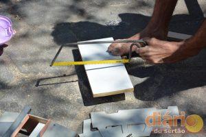 Geraldo fabricando carro de madeira com os pés
